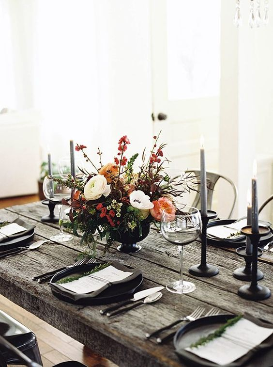 a rustic Halloween tablescape with a raw weathered wood table, grey candles, black chargrers and a textural floral centerpiece