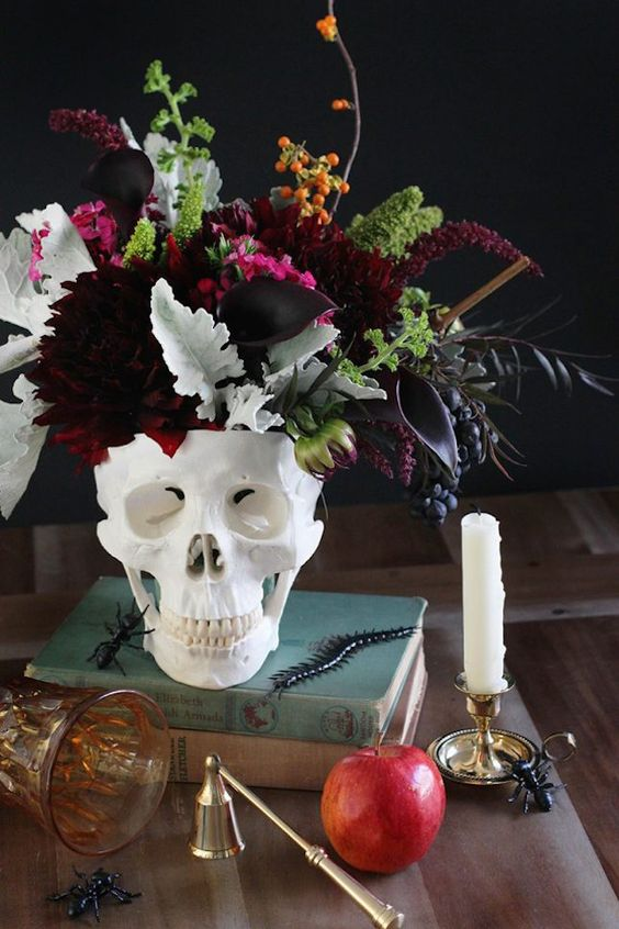 a stack of books, a skull with a dark floral arrangement with dark burgundy florals, pale and saturated greenery and berries
