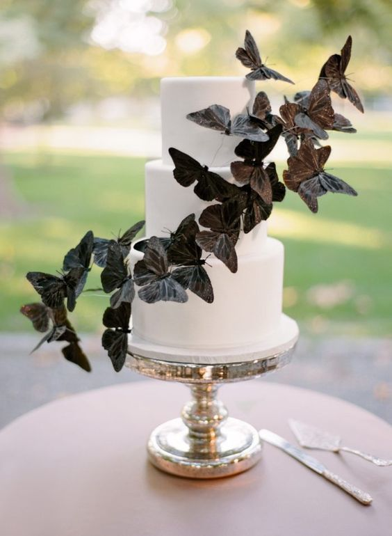 a white wedding cake decorated with large black butterflies for a timelessly elegant look