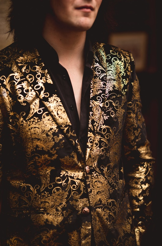 black pants, a black shirt and a bold gold and black patterned jacket for a wow effect