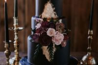 26 a matte black wedding cake with burgundy and blush sugar flowers served on a gold dish