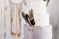 26 a matte grey and white wedding cake with gold foil and feathers for a boho wedding