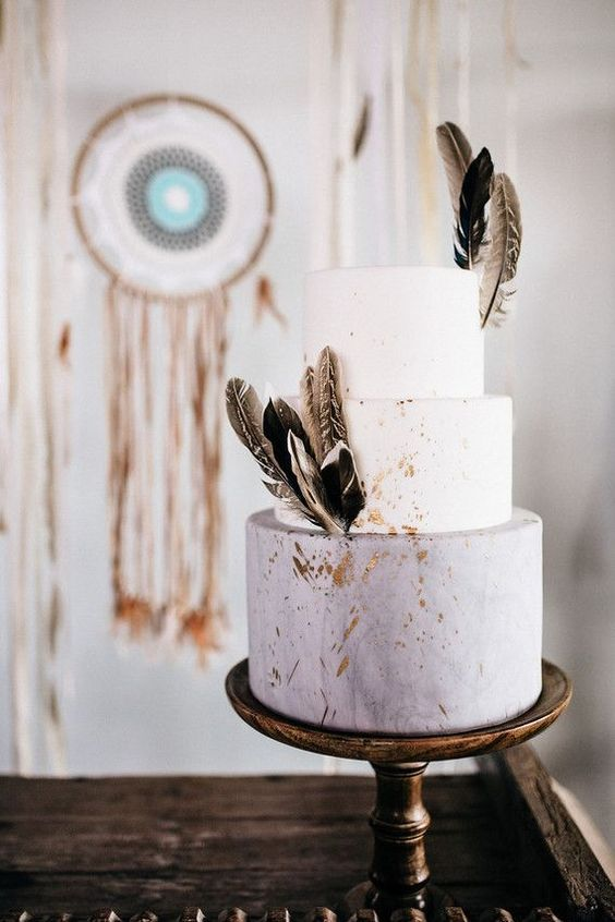 a matte grey and white wedding cake with gold foil and feathers for a boho wedding