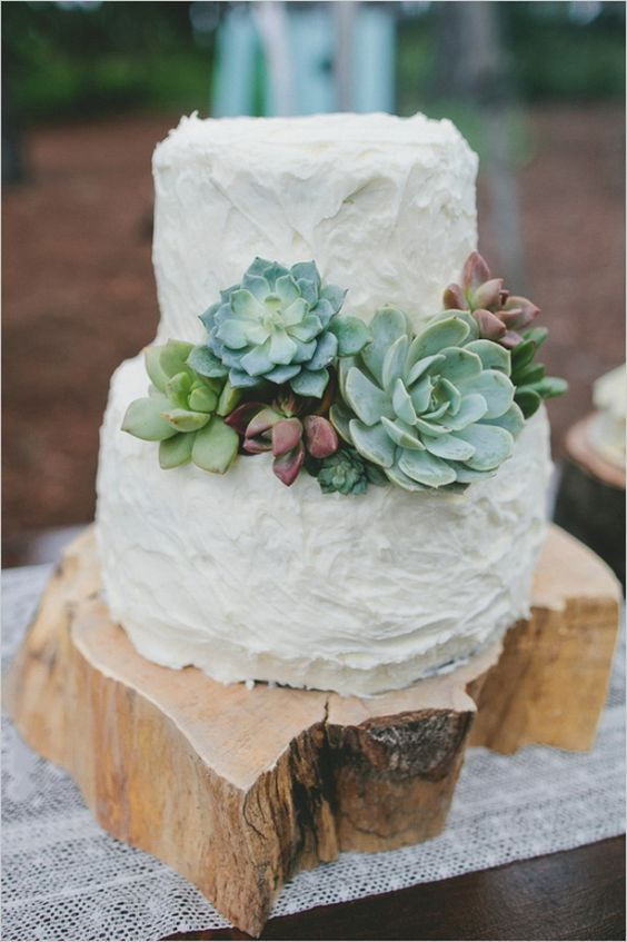 a rough wood stump cake stand highlight the uneven texture of the wedding cake