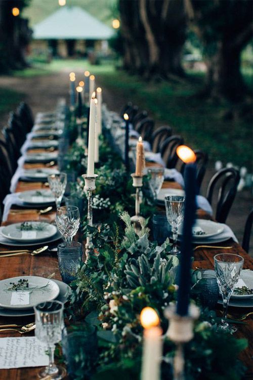 a simple moody tablescape with a textural greenery table runner, black, white and gold candles and matte grey plates