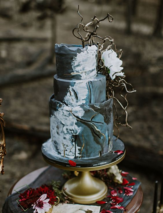 a wild woodsy Halloween wedding cake in grey and black, with white touches, branches and a white bloom