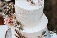27 a semi naked wedding cake with blush blooms, berries and feathers for a spring boho wedding