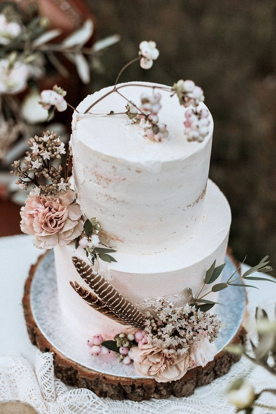 a semi naked wedding cake with blush blooms, berries and feathers for a spring boho wedding