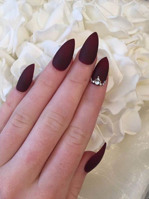 sharp matte burgundy nails adorned with bold rhinestones is a stunning idea for a Halloween bride
