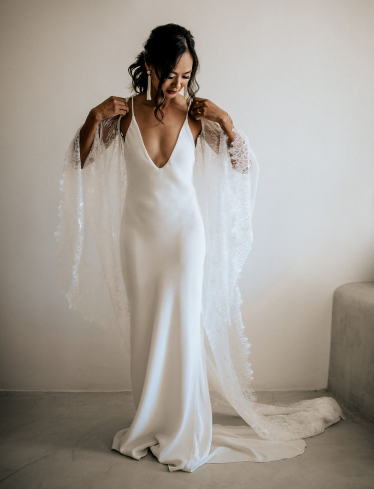 The bride was wearing a plain spaghetti strap wedding dress with a plunging neckline and an ethereal coverup