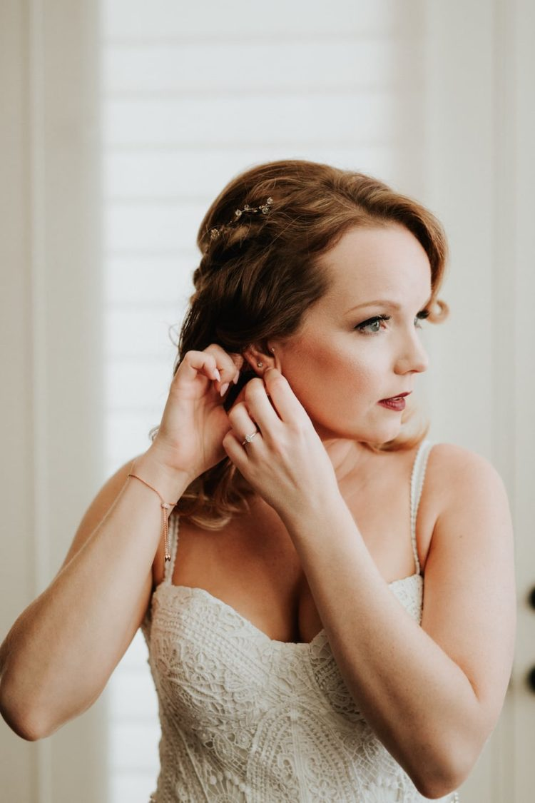 The bride was wearing a wavy half updo accented with a hair vine and a bold lip