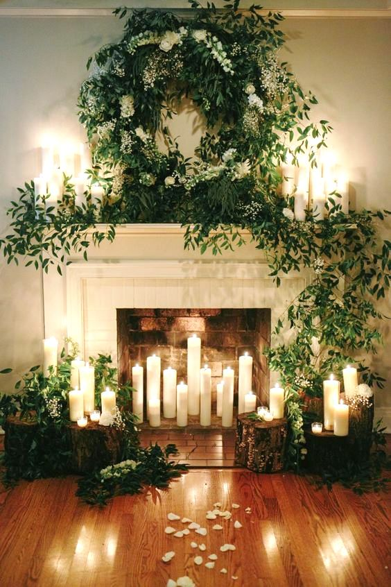 a beautiful fireplace with candles inside, around and on the mantel, with lush greenery and white blooms