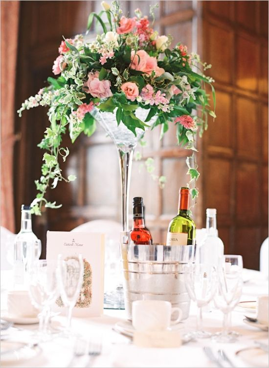 a chic wedding centerpiece of pink roses and cascadig greenery in a glass vase for a cool look