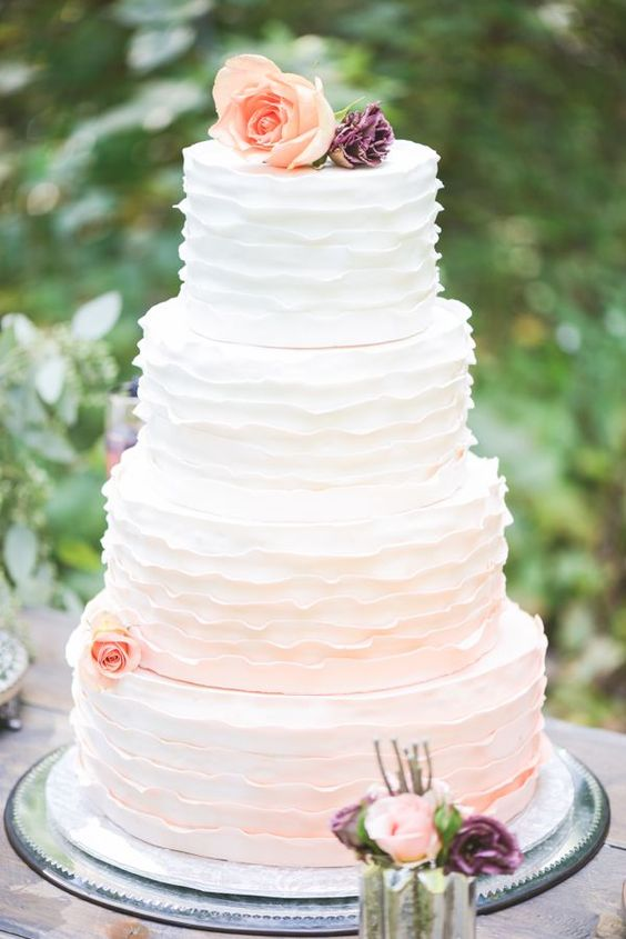 a subtle ombre ruffle wedding cake fro white to blush and with peachy blooms for decor