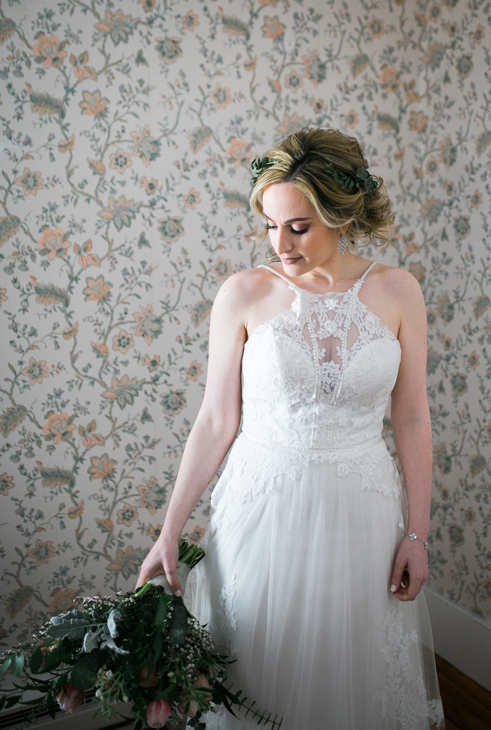 The bride was wearing a whimsy lace wedding gown with an illusion neckline and a train