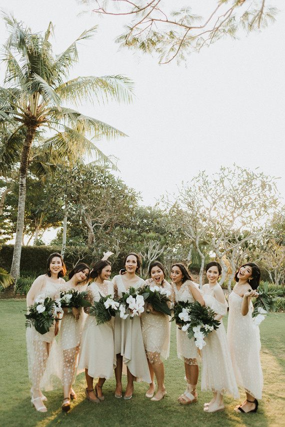 The bridesmaids were rocking off-white mismatching gowns with various necklines, silhouettes and sheer parts