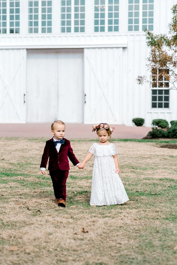 The flower girl was rocking a white lace maxi dress, and the ring bearer was wearing a maroon velvet suit