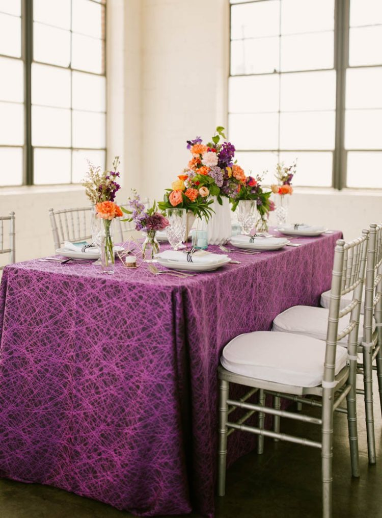 The wedding tablescape was done with a purple printed tablecloth, bright florals and geometric candle holders