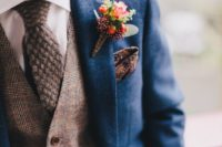 a blue suit with a brown checked waistcoat and a brown woollen necktie plus a patterned handkerchief