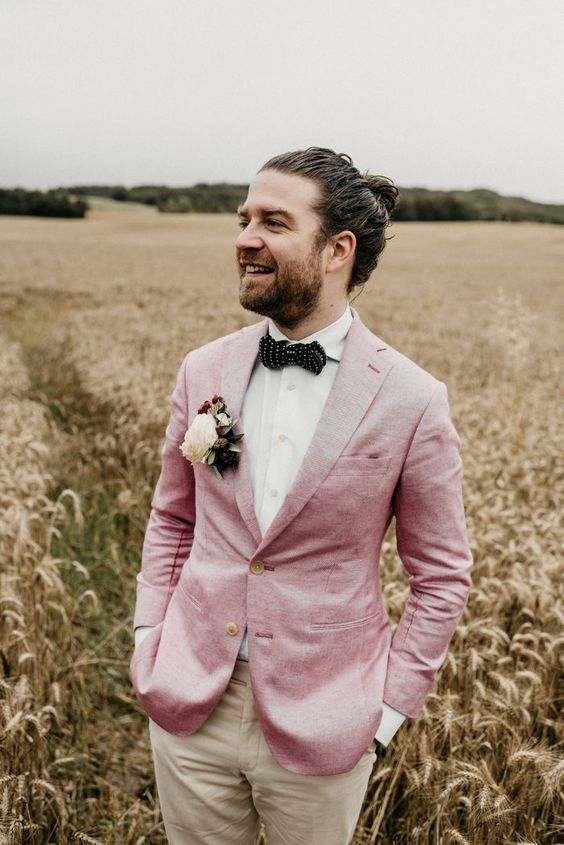 a relaxed and colorful groom's look with beige pants, a pink jacket and a polka dot bow tie for a modern fun wedding