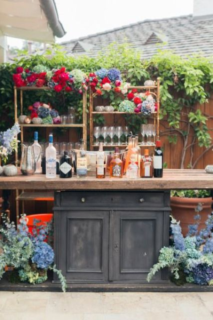 a wedding cocktail bar decorated with super bold florals that are used for wedding decor
