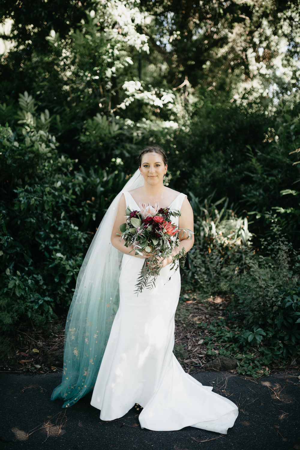 The bride was wearing a plain fit and flare wedding gown with a deep neckline and a gorgeous blue ombre veil