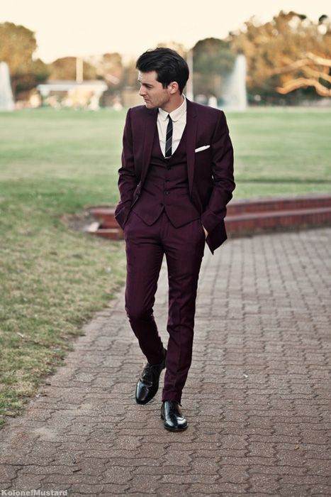 a burgundy three-piece suit with a striped tie is a great take on more formal wear