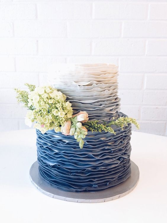 a chic ombre blue wedding cake decorated with real blooms and greenery is a trendy idea