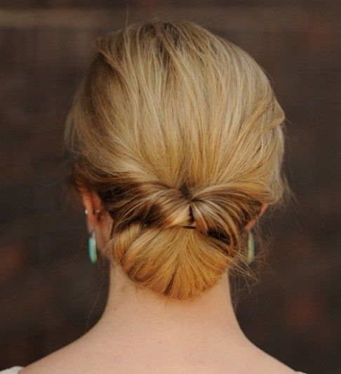 a low bun with a twist and a messy top for a refined and effortless look