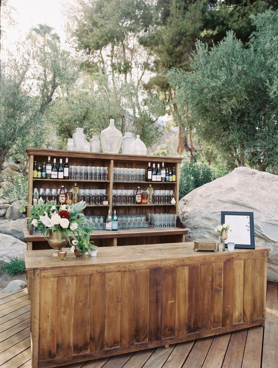 a rustic wedding cocktial bar decorated with little floral centerpieces and a large vases arrangement