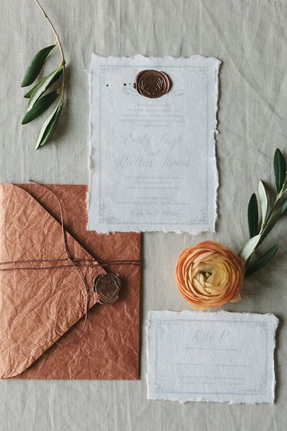vintage-inspired wedding invitaiton suite with deckle edge invites and a rust textural envelope