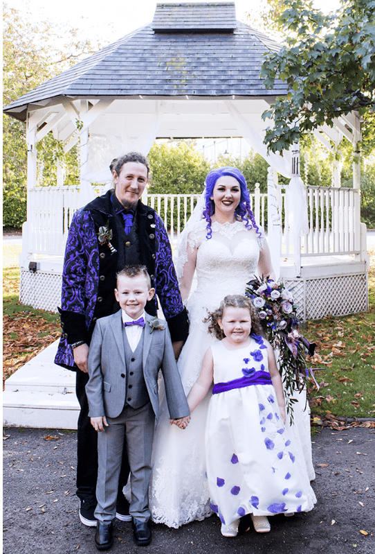 The groom was rocking a black suit with a purple patterned blazer and tie to match the wedding color scheme