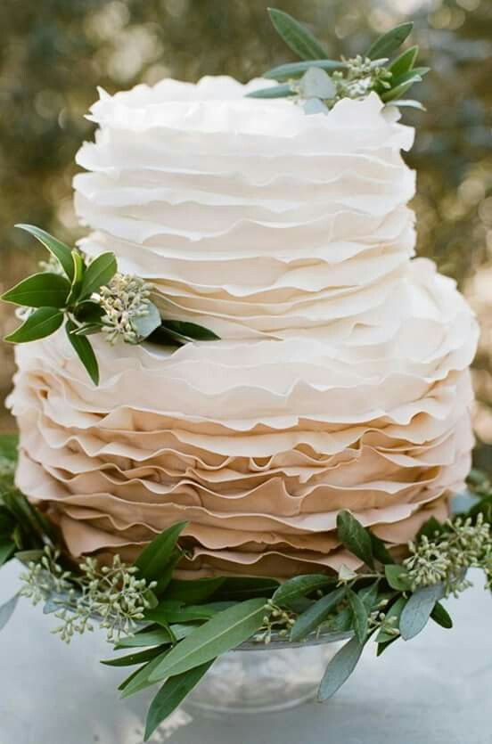 a cool ombre white to tan ruffle wedding cake decorated with seeded eucalyptus