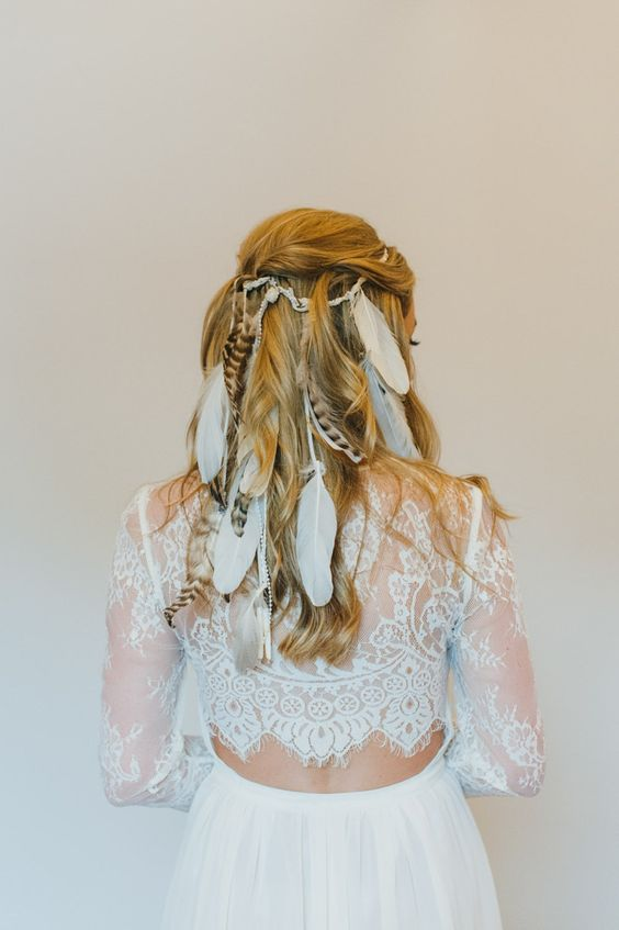 a half updo with a bump and waves spruced up with a lot of feathers for a boho feel