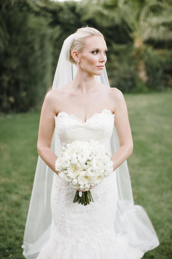 a lace strapless mermaid wedding dress with a train and a veil is great for a formal wedding