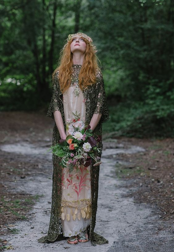 a neutral wedding dress with pink floral embroidery and a dark grene lace coverup with a train