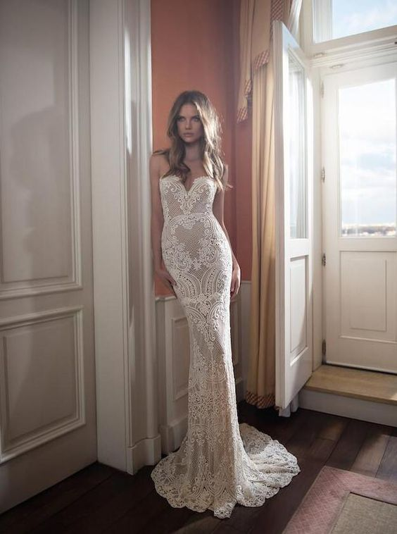 a strapless lace mermaid wedding gown with a deep neckline and a train for a sexy look
