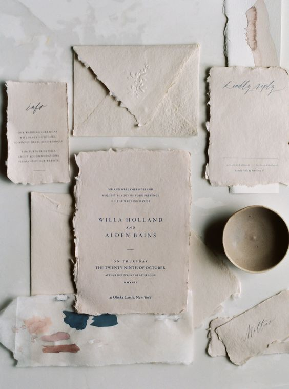 a vintage wedding invitation suite with a deckle edge and a textured envelope