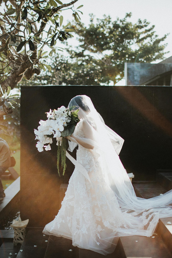 The bride was carrying a chic wedding bouquet with white orchids and much greenery