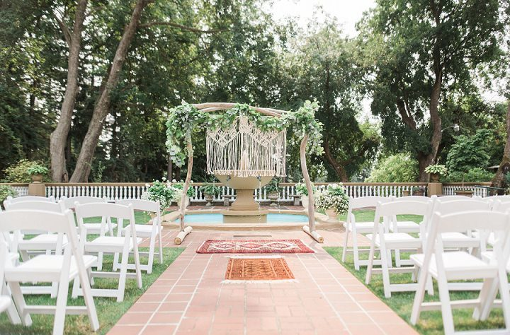The wedding ceremony space was outdoors, with a fountain and an arch of wood, greenery and macrame