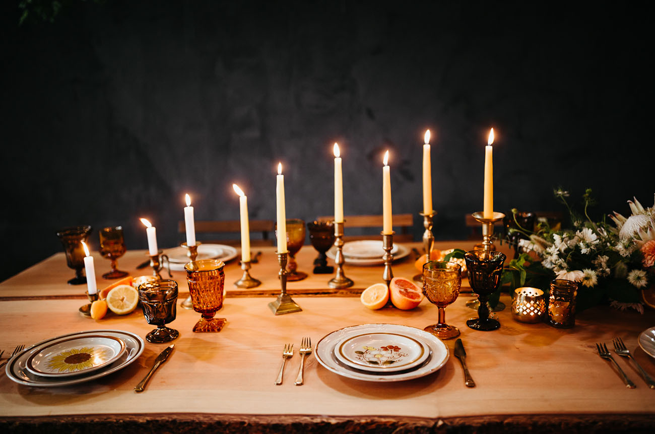 The wedding tablescape was done with vintage plates, colored glasses, candles and citrus