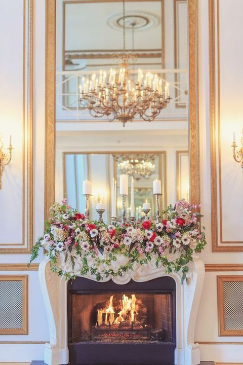 a chic refined fireplace with a real fire and candles plus lush colorful florals on on the mantel