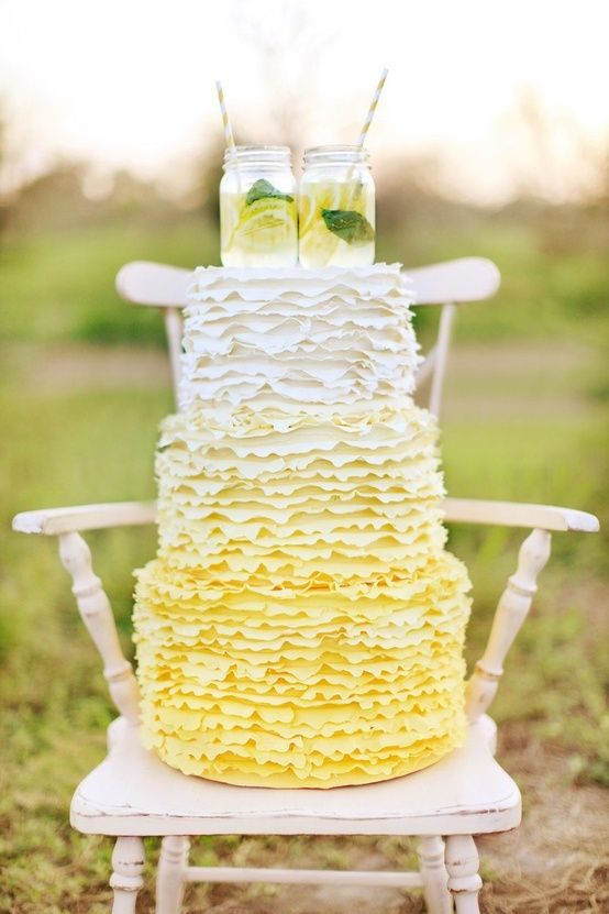 a fun ombre yellow ruffle wedding cake topped with mason jars with lemonade for a rustic wedding
