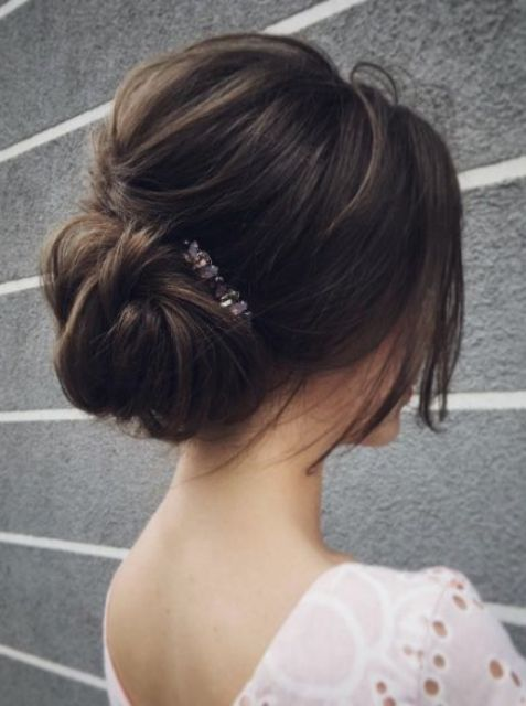 a messy low bun with a bump and some textural hair down plus a rhinestone hairpiece for an effortlessly chic look