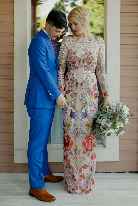 a sheath wedding gown with colorful embroidered flowers and lace appliques on the top