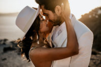07 The bride rocked trendy tassel earrings and a white hat for a boho feel