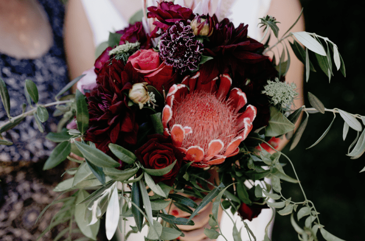 The bride was carrying a red, orange and burgundy wedding bouquet with much greenery