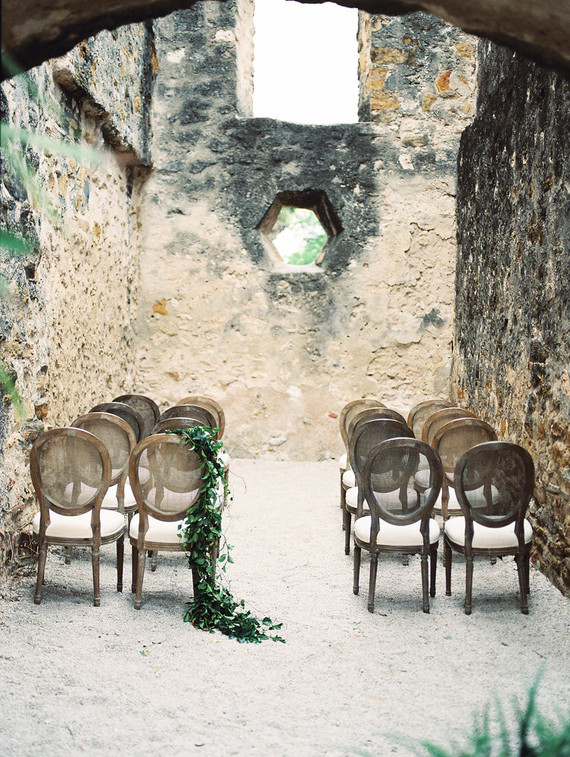 The ceremony space was in the Misson, with raw stone walls, refined vintage chairs decorated with greenery garlands