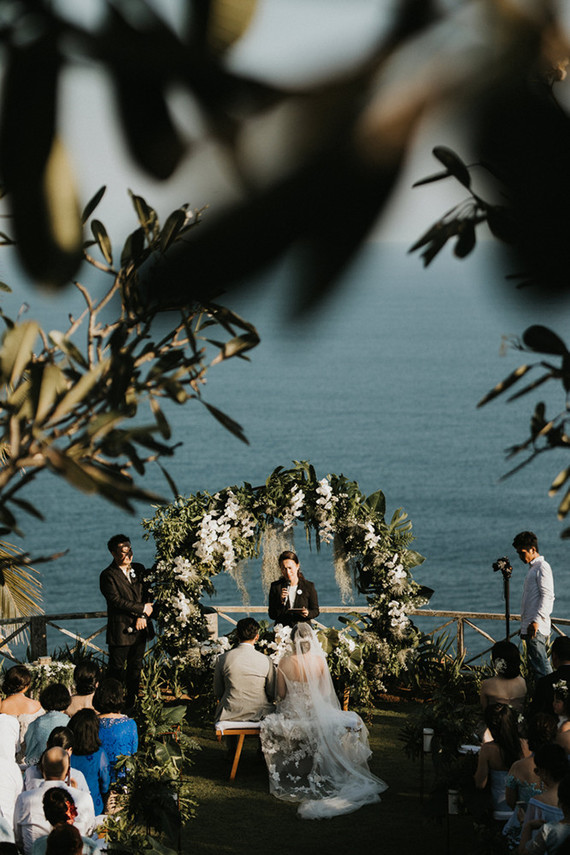 The ceremony took place on a terrace, with a gorgeous sea view and a lush floral arch with greenery