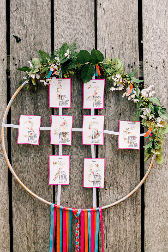 The wedding seating chart was done with bright frames, blooms, greenery and ribbons